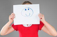 Foto Mädchen hält sich Blatt mit Smiley vors Gesicht