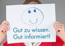 """Foto Mädchen hält sich Papier mit Aufschrift """"Gut zu wissen. Gut informiert"""" vors Gesicht"""