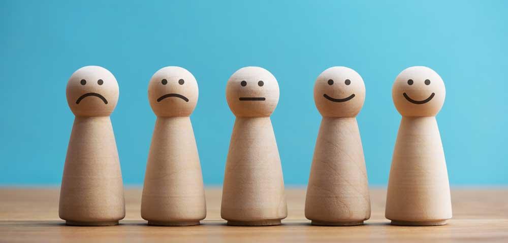 Holzfiguren mit traurigen und lachenden Gesichtern