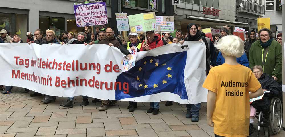 Gruppe trägt Plakat mit Aufschrift Tag der Gleichstellung