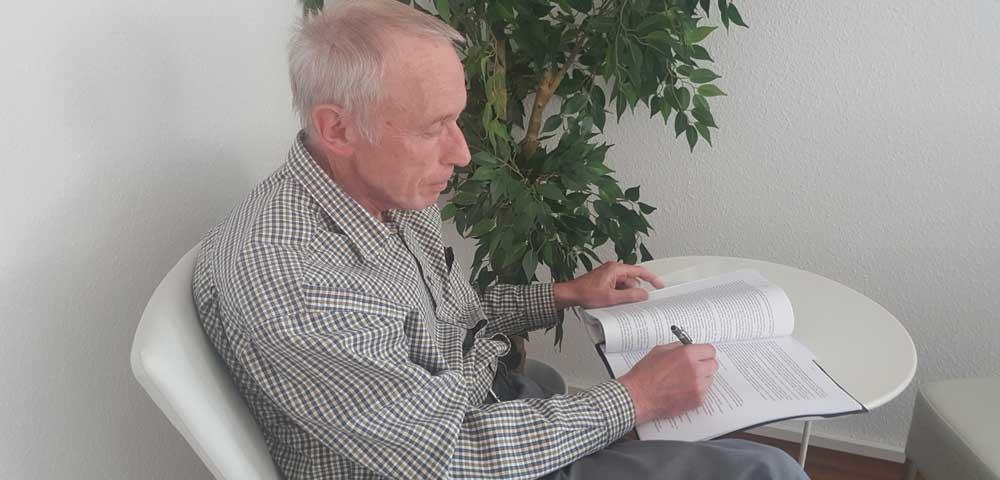 Werner Müller sitzt am Tisch vor seinem Manuskript