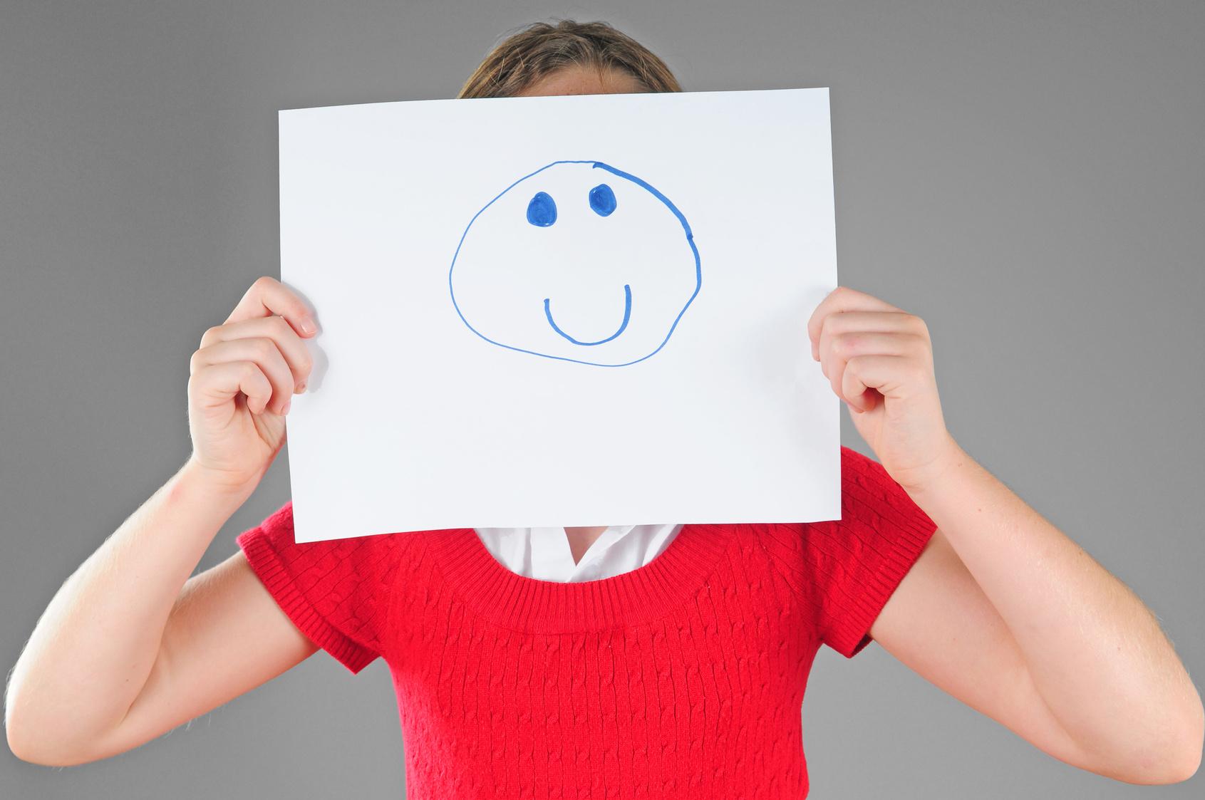 Mädchen hält sich Blatt Papier mit Smiley drauf vors Gesicht